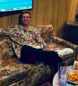 Garret from the bachelorette katies season sitting on a couch, with a sweater that matches the couch